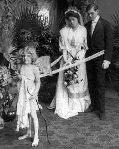 Child dressed as Cupid with ribbon around couple in wedding dress.(1905)