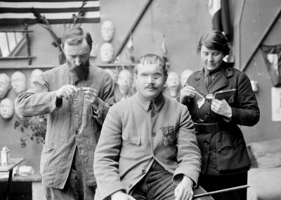 Mrs. Ladd and her assistant are working on a mask for a soldier whose face was mutilated in the war. His bravery won the Croix de guerre and the medaille militaire at the cost of his eye sight